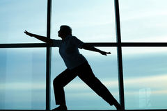 Exercise. Silhouette of female doing physical exercise on background of window Royalty Free Stock Photography