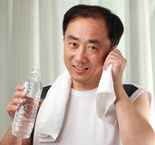 Exercise. Man with a bottle of water and a towel after exercise in a gym Stock Images