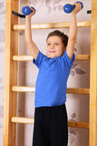 Exercise. The boy of preschool age lifts dumbbells in a domestic sports hall Stock Photography