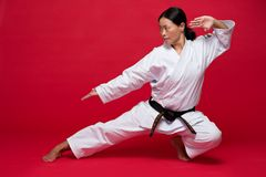 Exercise. Asian woman exercising karate on red background Stock Photos