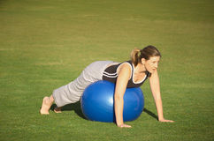 Exercise Ball. Female exercising in the park, using blue exercise ball Stock Photo