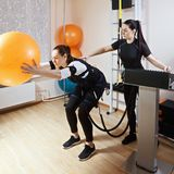 Exercise with ball. Couch assists athlete to make gymnastic ball exercise, supported with electric muscle stimulation purposed to increase effectiveness of Royalty Free Stock Images