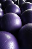 Exercise balls. Colored exercise balls with their reflections behind in a mirrored surface stock photos