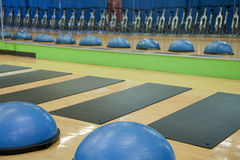 Exercise balls, mats and spin cycles. Bosu exercise balls, stretching mats and stationary spin bicycles as would be found in a gym or health club stock images