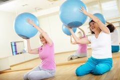 Exercise with balls. Portrait of sporty females doing physical exercise with fitness balls in sport gym Royalty Free Stock Photo