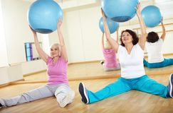 Exercise with balls. Portrait of sporty females doing physical exercise with fitness balls in sport gym Royalty Free Stock Image