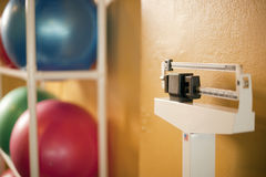 Exercise balls and Scale in health club. Exercise balance balls and scale in a gym Royalty Free Stock Photos