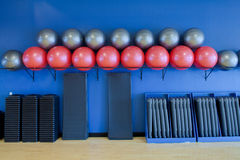 Exercise balls, stretching mats and aerobic steps. Shown in a blue room with wood floors, as would be found in a gym or health club Royalty Free Stock Images