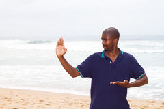 Exercise on beach. Young african american man practicing kung fu exercise on beach Stock Photo