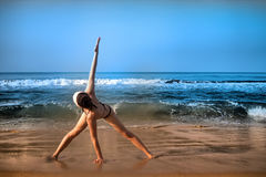 Exercise on beach girls yoga trainer at home yoga. Royalty Free Stock Photo