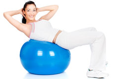 Exercise on the big blue ball. Happy girl doing exercise on the big blue ball, isolated on white Royalty Free Stock Image
