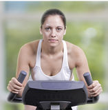 Exercise Bike. An attractive caucasian woman on an exercise maching at the gym Royalty Free Stock Photos