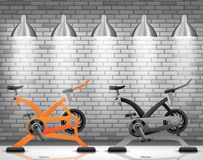 Exercise bike with light spotlight on brick wall texture background Stock Images