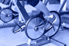 Exercise bike with spinning wheels - woman biking Stock Image