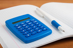 On the exercise book into a cell lying blue calculator and pen. Stock Image