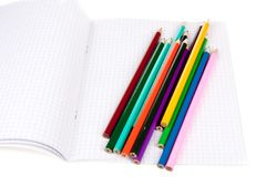 Exercise book with colorful pencils Royalty Free Stock Images