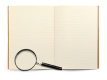 Exercise book and magnifying glass Royalty Free Stock Photography