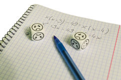 Exercise book with mathemacical equation and dices with sad face Royalty Free Stock Image