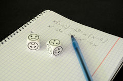 Exercise book with mathematical equation and dices with sad face Royalty Free Stock Photos