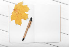 Exercise book with pen and autumn leaves. Stock Photo