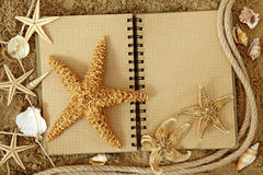 Exercise book and sea stars. On sand Stock Photos