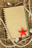 Exercise book and sea stars. On sand Stock Image