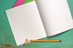 Exercise books and pencils. Opened exercise books and pencils on the desk, top view Royalty Free Stock Photos