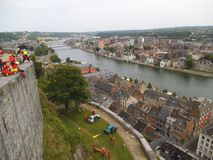 Exercise for car accident with rope rescue on a hill in Namur. A high stone wall with red dressed climbing persons and the city with the river in the stock photos