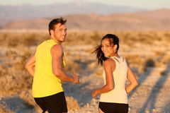 Exercise - couple running looking happy stock photo