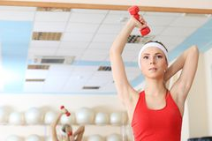 Exercise with dumbbells. Young sporty woman in the gym centre Royalty Free Stock Photo
