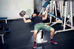 Exercise with dumbbells - wiring in the sides on an incline bench. Old gym room Royalty Free Stock Images