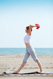 Exercise with dumbell. Woman doing exercise with dumbell on beach Royalty Free Stock Photos