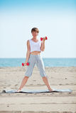 Exercise with dumbell. Woman doing exercise with dumbell on beach Stock Images
