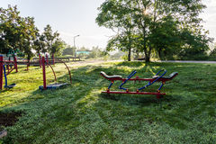 Exercise equipment in public park on sunrise. Royalty Free Stock Images