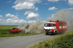 Exercise firemen, demonstration of fire extinguishing of car Stock Images
