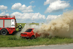 Exercise firemen, demonstration of fire extinguishing of car Royalty Free Stock Image