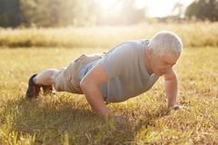Exercise, fitness, age and workout concept. Healthy sporty mature male has physical exercises outdoor in early morning, makes plan. K on ground, expresses his Royalty Free Stock Photography