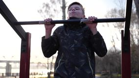 Exercise in the fresh air. Young strong guy doing exercises on the bar. Autumn park stock video