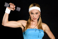 Exercise girl. Woman exercising with a small weight... showing off her muscular arm stock image