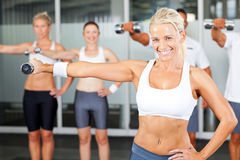Exercise in gym. Group of people exercise in gym with dumbbells Stock Images