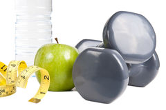 Exercise and Healthy Diet. Pair of dumbbells, green apple, measuring tape and bottle of water. Exercise and healthy diet concept Royalty Free Stock Photography