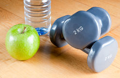 Exercise and Healthy Diet. Pair of dumbbells, green apple, measuring tape and bottle of water. Exercise and healthy diet concept Stock Photo