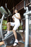Exercise at home. Girl is exercising at home using bicycle Stock Photography