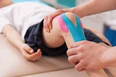 Exercise for knee. Physiotherapist doing with child exercise for knee stock images