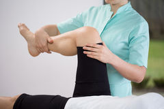 Exercise for lower limb. Close-up of physiotherapist doing exercise of lower limb royalty free stock photo