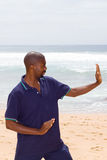 Exercise man. Young african american man doing tai chi exercise on beach Stock Image