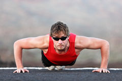 Exercise man training push ups. Doing strength training outdoors. Fit muscular male fitness model Royalty Free Stock Photos