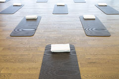 Exercise mats in fitness center. Exercise or yoga mats on wooden floor in empty fitness center Royalty Free Stock Images