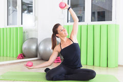 Exercise with rubber weights. Girl doing pilates in studio royalty free stock photos