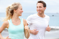 Exercise running couple jogging on beach talking. And training as part of healthy lifestyle. Two fit runners jogging happy and smiling during workout Royalty Free Stock Photos